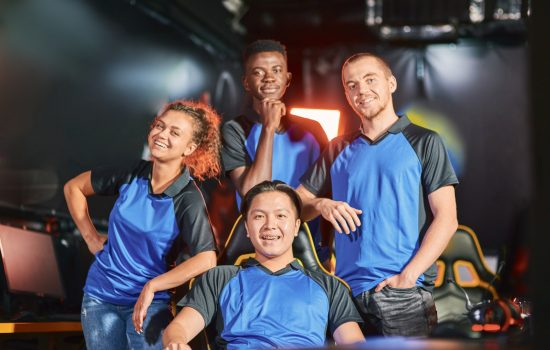 happy-multiracial-cybersport-team-smiling-at-camera-after-esport-tournament.jpg